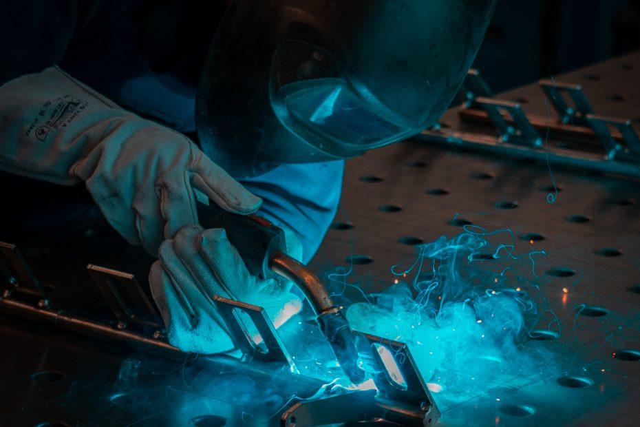 Ein Schweißer, der verschiedene Bauteile aus Metall verbindet.